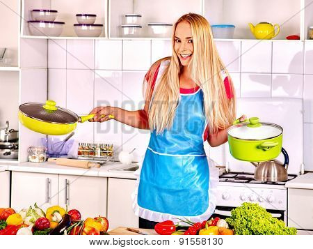 Happy blond woman in blue apron preparing food at kitchen.