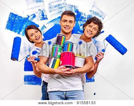 Happy three persons are painting  wall at home.