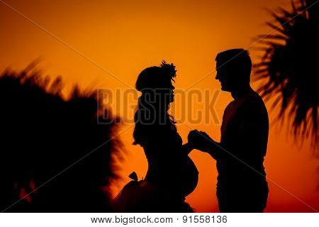 Silhouette of young couple expecting baby holding hands during orange sunset
