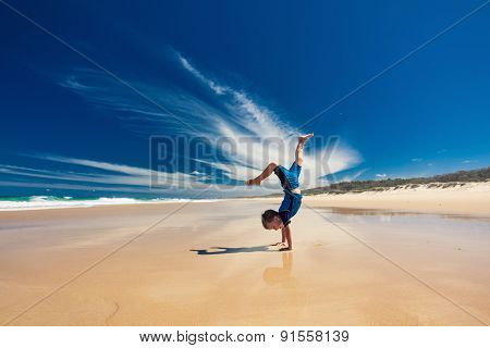 Acrobatic young boy performing hand stand on the empty beach