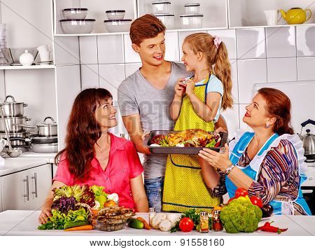 Happy family with kid and grandmother at kitchen. Cooking chicken.
