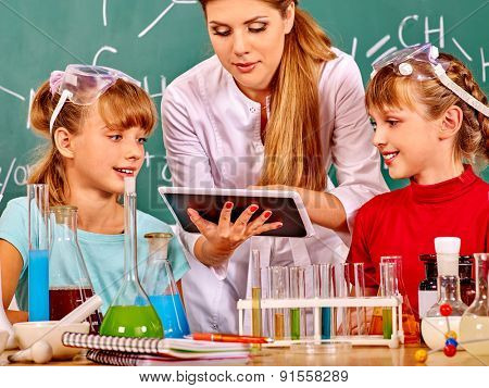 Kids with teacher  holding tablet pc in chemistry class.