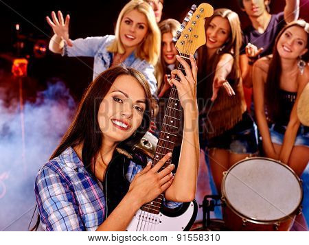 Musical group playing in night club. Male and female and steam.