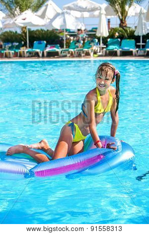 Little girl swimming on inflatable beach mattress. One person