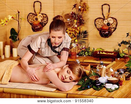Young sleeping woman getting massage in bamboo spa.
