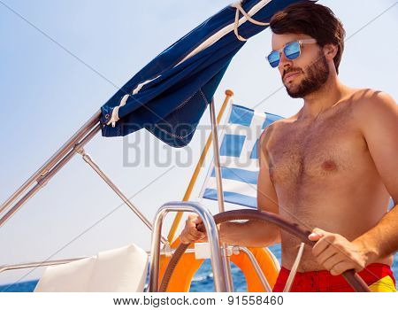 Handsome man driving sailboat, active lifestyle, having fun in the sea in bright sunny day, enjoying happy summer vacation