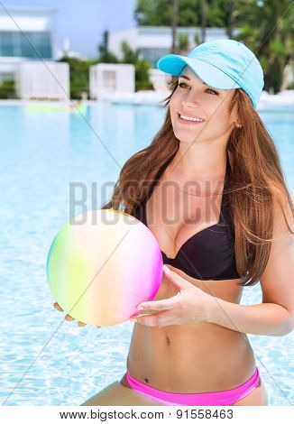 Happy woman with ball standing in swimming pool, having fun on beach resort, enjoying summer activity, playing water game, vacation and enjoyment concept