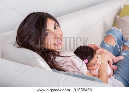 Beautiful mother with little baby daughter resting on the couch at home, enjoying motherhood, happy young family, parent's love concept
