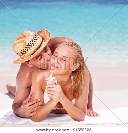 Loving couple lying down on the sandy coast, handsome man kissing his cute girlfriend, enjoying honeymoon vacation on beach resort