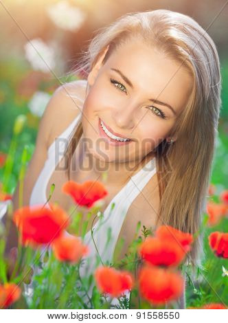 Beautiful woman lying down on fresh red poppy flowers field, enjoying beauty of countryside nature, relaxation and pleasure in the summer garden