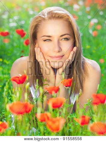 Nice girl relaxing on fresh red poppy flower meadow, enjoying beauty of spring blooming, freedom and enjoyment concept
