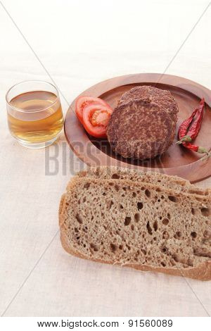 fresh beef meat hamburger on wooden plate with cutlery and rye bread bun on tablecloth with whiskey shot