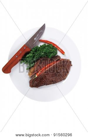 grilled beef steak meat with red hot pepper and fresh raw kale leaf served on white plate isolated over white background