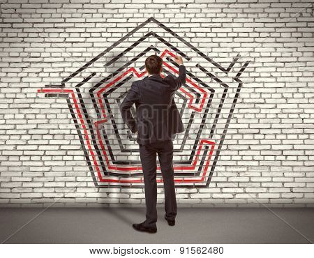 Business concept. Back view of businessman drawing labyrinth on wall