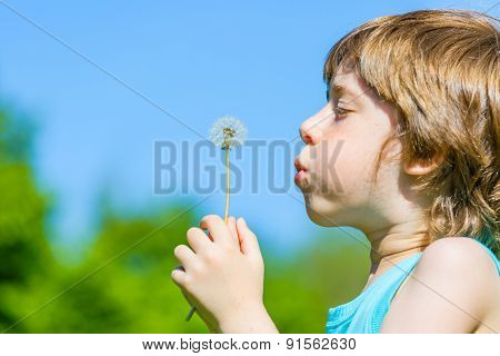 Kid blowing dandelion