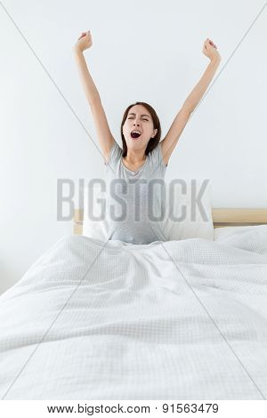 Woman yawning on the bed and hand stretching