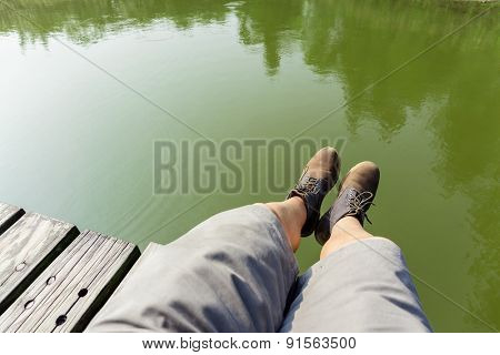 Man legs sitting on wooden path