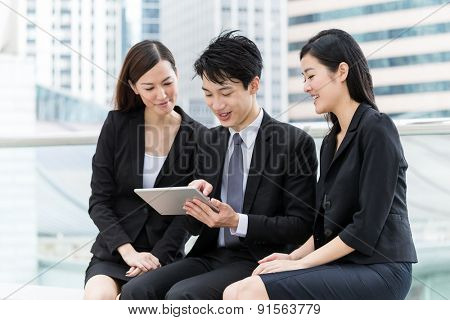 Business teammate use of digital tablet together