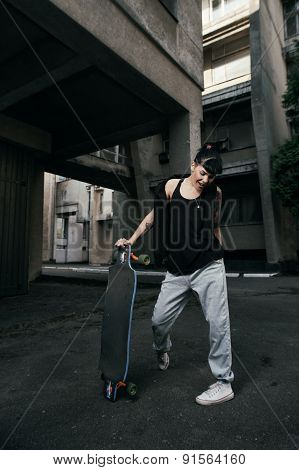 black haired tattooed lady stands with longboard in backyard