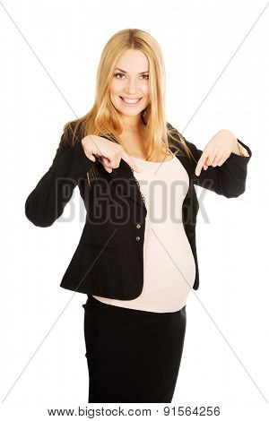 Smiling pregnant woman pointing on her belly.