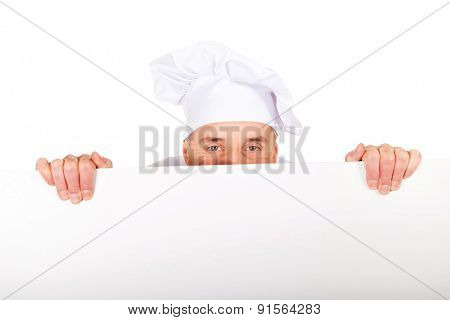 Experienced chef in white uniform holding empty banner.