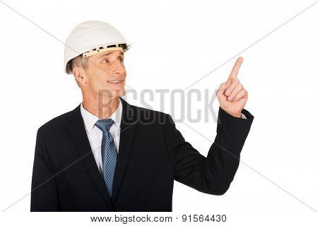 Smiling mature engineer with hard hat pointing up.