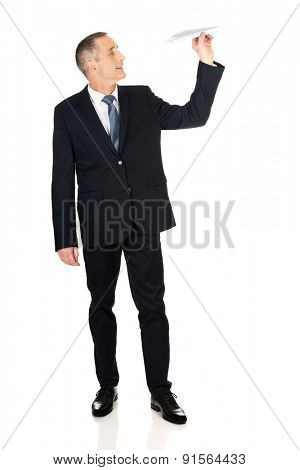 Full length businessman throwing a paper plane.