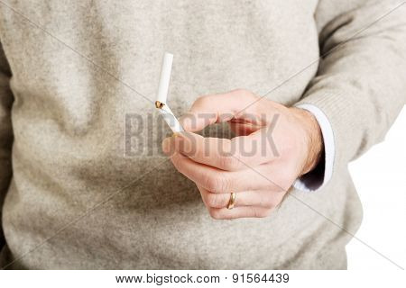 Close up on male hand with broken cigarette.