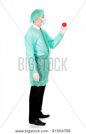 Full length side view of male doctor holding heart model.