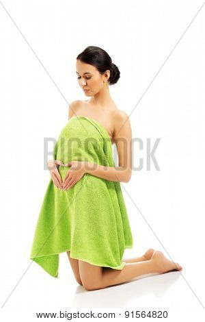 Woman kneeling wrapped in towel, making heart shape