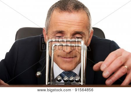 Businessman in office playing with newton balls.