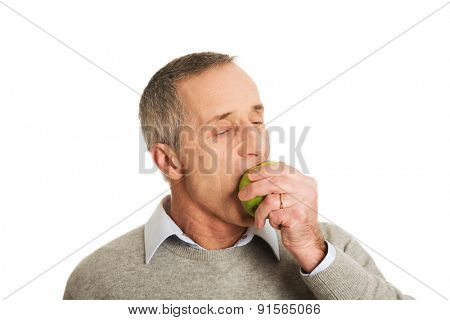 Portrait of mature man eating an apple.