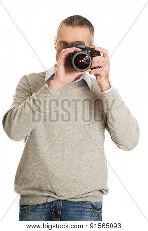 Mature man with professional photo camera.