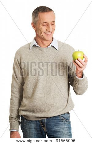 Happy mature man with an apple.