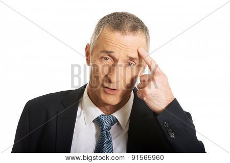 Portrait of businessman gesturing with finger against temple