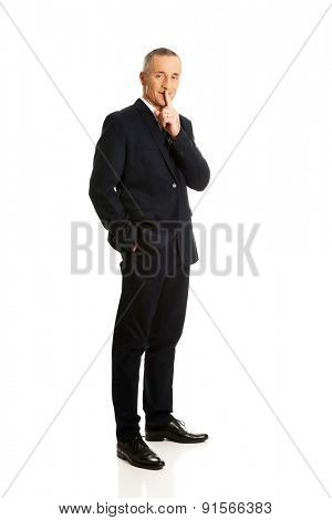 Full length businessman gesturing silent sign.