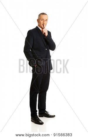 Full length businessman gesturing silent sign.