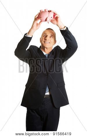 Cheerful mature businessman holding piggybank.