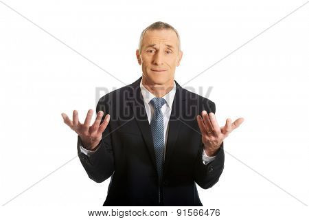 Businessman with hands open in undecided gesture.