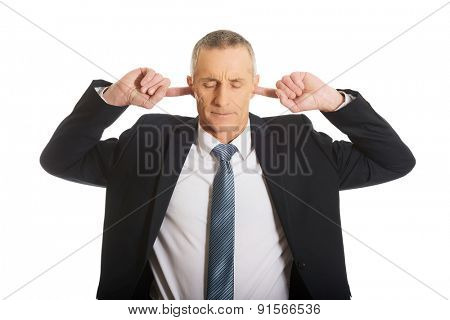 Portrait of businessman plugging his ears.
