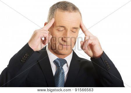 Portrait of a pensive businessman touching head.