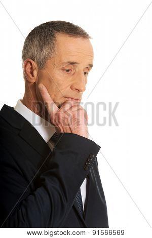 Portrait of a pensive businessman touching chin.