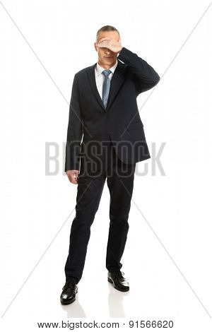 Full length stressed businessman covering his face.