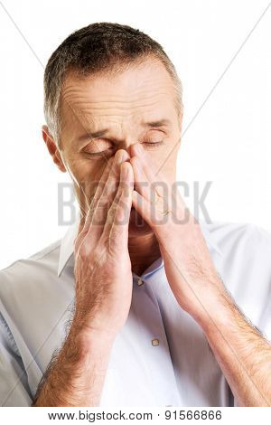 Mature man suffering from sinus pressure pain.