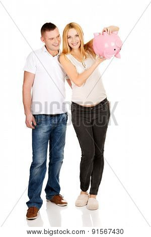 Pregnancy couple with piggy bank