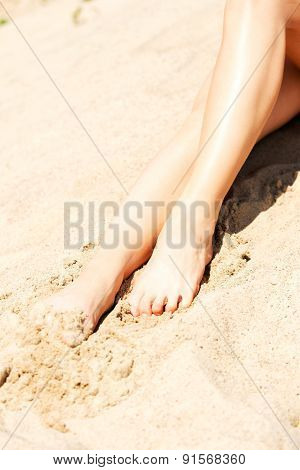 Woman's legs on the sand by the sea
