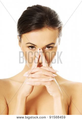Portrait of serious nude woman holding nose and looking at the camera.