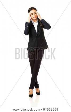 Full length businesswoman having huge headache.