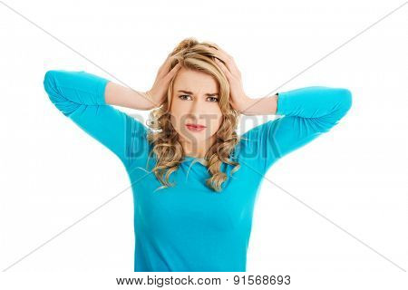 Portrait of young woman with huge headache.