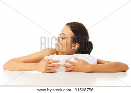 Nude woman trying to rest her head on a rolled towel.